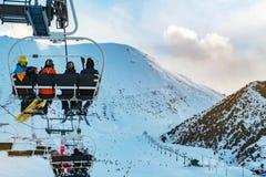 Makro des grünen Grases Skifahrer auf Fahrten eines Sesselliftes stockfotografie
