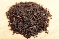 Makro des schwarzen Tees auf hölzernem Vorstand Lizenzfreie Stockfotos