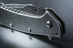 Makro des a-Stellungs-Griffs eines schwarzen geschlossenen faltenden Messers mit Reflexion auf dunklem Boden Lizenzfreie Stockbilder