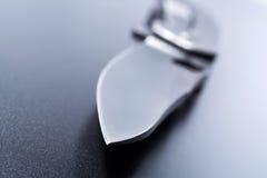 Makro einer Messerspitze eines geöffneten Militärmessers, das auf dunklem Boden liegt Stockbilder