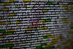 Makro- fotografia ekran komputerowy z programa źródła kodem i podkreślająca MALWARE inskrypcja w środku Pismo na fotografia stock