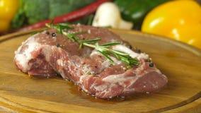 Makro- fotografia mięso marynował z pikantność kłama na round drewnianej desce, obracanie deska, boczny widok przy zbiory