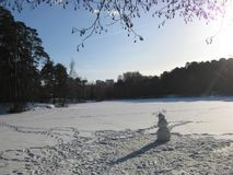 Makro- fotografia z dekoracyjnym krajobrazowym tłem Pogodny weekend na zamarzniętym miasta jeziorze z białym śniegiem i bałwanem obraz stock