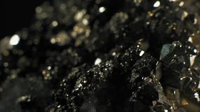 Makro-, glänzende Kristalle von Pirita auf einem schwarzen Hintergrund stock footage