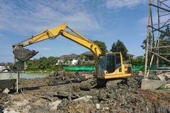 Makro grävskopaarbete som justerar yttersida för konstruktionsplats lastbil för arbetekontrollmakro som tar bort jord och smuts K royaltyfri fotografi