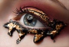 Makro- i zakończenie kreatywnie makijażu temat: piękny żeński oko z czerwień cieniami i złotem, czarna farba, retuszująca fotogra Zdjęcia Stock