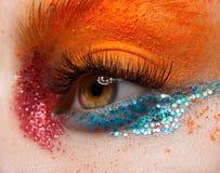 Makro- i zakończenie kreatywnie makijażu temat: Piękny żeński oko z czerwonym i błękitnym błyska i pomarańczowy pigment Fotografia Stock
