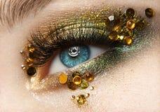 Makro- i zakończenie kreatywnie makijażu temat: piękny żeński oko z złotymi cieniami i żółtymi diamentami, retuszująca fotografia Zdjęcia Royalty Free