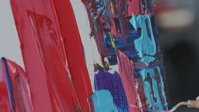 Makro- krótkopęd brezentowa tekstura z świeżymi akrylowymi colourful farbami Żeńska ręka ostrożnie stosuje farbę z szpachelką