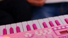 Makro- mała dziewczynka palca pras klucze na menchiach bawją się pianino zbiory