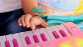 Makro- mała dziewczynka palec dokazuje na różowej fortepianowej klawiaturze zdjęcie wideo