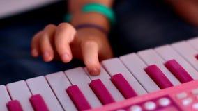 Makro- mały palec naciska klucze na różowym pianinie jeden jeden zdjęcie wideo