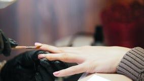 Makro- manicure w piękno salonie kropi gwoździ cekiny - mistrz transakcje poleruje na gwoździach - zbiory
