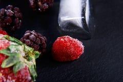 Makro- marznąca malinka, czernica, truskawka nowi liście, kawałki lód na czarnego iłołupka desce, marznąca owoc, ustawia Zdjęcie Stock