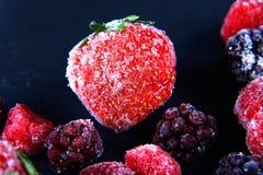 Makro- marznąca malinka, czernica, truskawka nowi liście, kawałki lód na czarnego iłołupka desce, marznąca owoc, ustawia Fotografia Stock