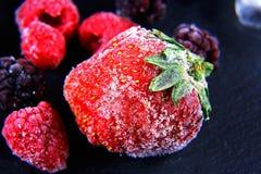 Makro- marznąca malinka, czernica, truskawka nowi liście, kawałki lód na czarnego iłołupka desce, marznąca owoc, ustawia Zdjęcie Royalty Free