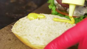 Makro-Person Pours Mustard auf Brötchen für das Kochen des Hamburgers stock video