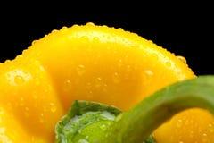 Makro schnitt Schuss des gelben Hintergrundes des grünen Pfeffers mit Wassertropfen Lizenzfreies Stockbild