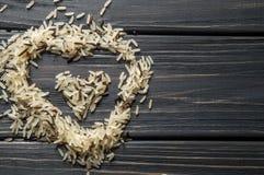 Makro slut upp Hjärta formad kulle av lösa ris på en mörk träbakgrund asiatisk kokkonst royaltyfria foton
