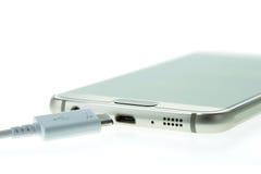 Makro-Smartphone schließen an das Ladegerät an, das auf Weiß lokalisiert wird lizenzfreie stockfotos