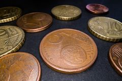 Makro som skjutas av euromynt på svart bakgrund Stäng sig upp av bakgrund för kassa för metallcirkelmynt Sparande pengar, inv royaltyfria bilder