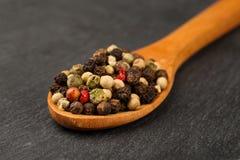 Makro- strzał czerni, zieleni, bielu i czerwieni peppercorn mieszanka w drewnianej łyżce na ciemnej kamiennej kuchni, wsiada głęb obraz stock