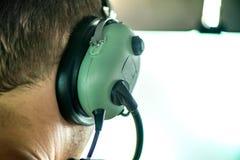 Makro- strzał pilotowa jest ubranym lotnictwo słuchawki, opowiadać z dyspozytorem i latanie z małym samolotem i obrazy royalty free