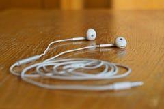 Makro- szczegół białe nowożytne słuchawki w futurystycznym projekcie na drewnianym tle jako symbol słuchanie muzyka zdjęcia royalty free