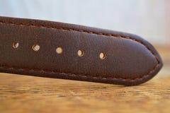 Makro- szczegół brown rzemienna wristwatch patka na drewnianym tle obrazy royalty free
