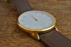 Makro- szczegół luksusowy złoty wristwatch z białą tarczą na drewnianym tle jako symbol drogi timepiece i zdjęcia stock