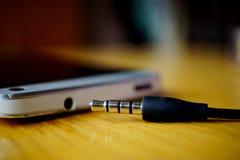 Makro- szczegół metalu hełmofonu dźwigarka w pobliżu włącznik w telefonie komórkowym na drewnianej powierzchni, fotografia stock