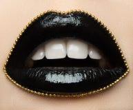 Makro- und kreatives Make-upthema der Nahaufnahme: schöne weibliche Lippen mit schwarzem Lippenstift und einer Goldkette entlang  Lizenzfreie Stockbilder