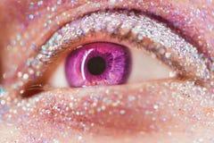 Makro violettes oder rosa weibliches Auge mit Funkelnlidschatten, bunte Funken, Kristalle Schönheitshintergrund, Modezauber lizenzfreies stockfoto