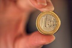 Makro von einer Euromünze zwischen weiblichen Fingern Stockfoto