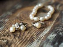 Makro- von schönen Perlenohrringen und Braut schellen auf hölzernem Hintergrund Stockfotos