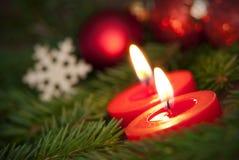 Makro von zwei brennenden Kerzen mit Weihnachtshintergrund Lizenzfreies Stockbild