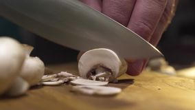Makro- wideo kucharz pokrajać surowych szampiniony na drewnianej desce, gotuje pieczarki, jarski jedzenie, makro- jedzenie zdjęcie wideo