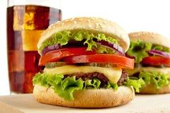 Makro- widok cheeseburgers i szkło kola na drewnianej desce Zdjęcie Royalty Free