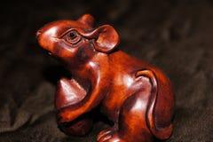 Makroansicht einer netten hölzernen geschnitzten braunen Poliermaus auf einem dunklen Material Stockfotos