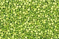 Makrobakgrundstextur av vibrerande gröna torkade delade ärtor Arkivfoto