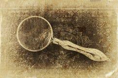 Makrobild av förstoringsglaset över antikvitetsvarträkningen retro filtrerad bild, foto för gammal stil Arkivfoto