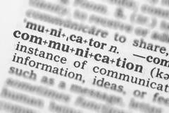 Makrobild av ordbokdefinitionen av kommunikationen Arkivbild