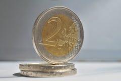 Makrodetail einer silbernen und goldenen Münze im Wert von zwei Euros EUR, von Euro auf Weiß und von Silberhintergrund als Symbol Stockbilder