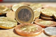 Makrodetail eines Stapels der Münzen auf der Holzoberfläche mit einem Silber und einer goldenen Euromünze trennte sich von andere Stockbilder