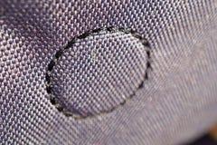 Makrodetalj av en cirkel som göras av den sydde tråden på det glansiga tyget Royaltyfri Bild