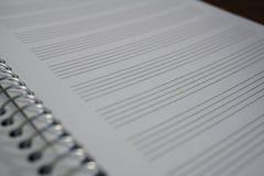 Makrodetalj av en notepad med papper som fodras som pianoarket med linjer som är förberedda för att komponera musik Royaltyfria Foton
