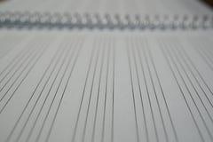 Makrodetalj av en notepad med papper som fodras som pianoarket med linjer som är förberedda för att komponera musik Arkivbilder