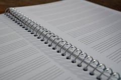 Makrodetalj av en notepad med papper som fodras som pianoarket med linjer som är förberedda för att komponera musik Arkivfoto