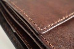 Makrodetaljen av en vit- och brunttråd som syr sydde svart och brunt, piskar plånboken Arkivbilder