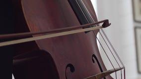 Makrodetaljen av musikinstrumentet, cellist spelar på rader med till och med en pilbåge lager videofilmer